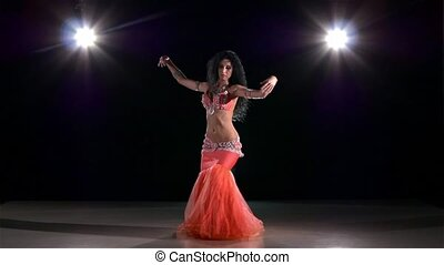 Young belly dancer girl dancing exotic on black, back light, slow motion