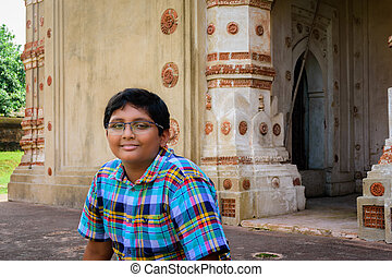 Young Bengali boy in front of Ancient Hindu terracotta temples of worship of Bengal with copy space