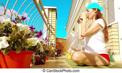 Young beutiful woman drinking tea or coffee on the sunny terrace