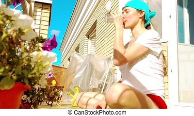 Young beutiful woman drinking water on the balcony after fitness or yoga