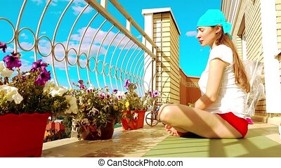 Young beutiful woman relaxing on the balcony after fitness or yoga
