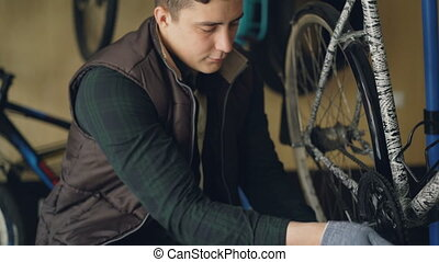 Young bicycle repairer is fixing bike treadle mechanism...