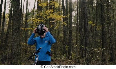 Young bicycle rider outside in autumn nature. - Young...