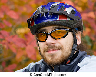 Young bicycler on the background of autumn leaves (portrait,...