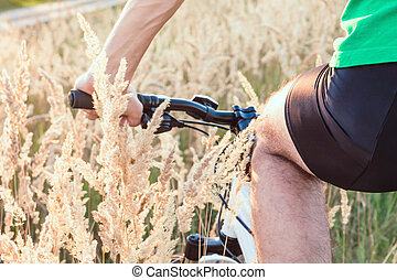 Young bicyclist riding in the field