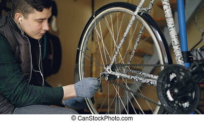 Young bike repairing master is adjusting wheel mechanism...