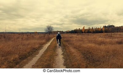 young biker cycling on a dirt field road - Aerial of young...