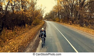 young biker cycling on a road with a scenic autumn forest -...