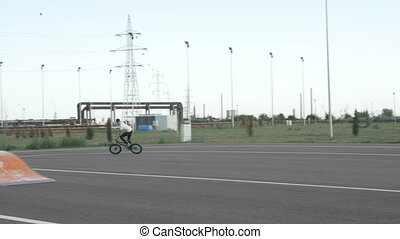 Young biker pedaling over a ramp in a recreational area