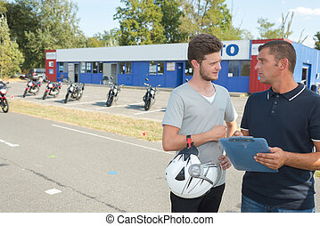 Young biker talking to instructor of motorcycle training course