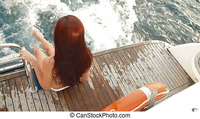 Young bikini woman enjoying summer vacation on a yacht
