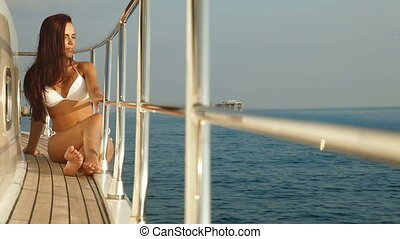 Young bikini woman enjoying summer vacation on deck of yacht