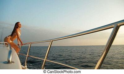 Young bikini woman enjoying summer vacation on deck of yacht in Mediterranean Sea