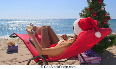 Young bikini woman spends Christmas vacations on a warm beach