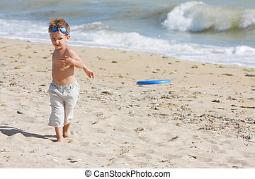 young biy playing frisbee on beach
