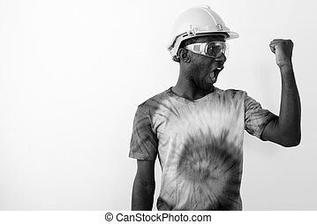 Young black African man construction worker wearing hard hat and safety glasses while flexing his bicep