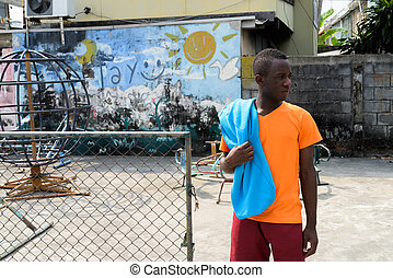 Young black African man thinking while holding jacket over his s