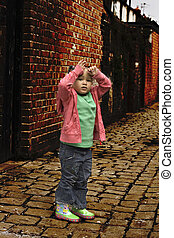 Young black baby girl playing on cobble stoned alley
