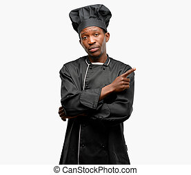 Young black cook wearing chef hat pointing away side with finger
