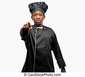 Young black cook wearing chef hat pointing to the front with finger