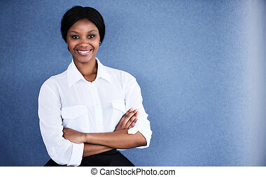 Young black female student smiling at camera with arms crossed