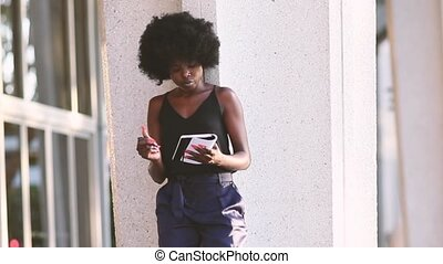 Young black girl writing in her notebook standing in the...