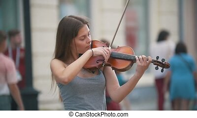 Young black hair woman playing a violin at the pedestrian...