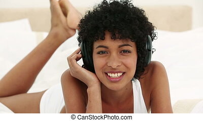 Young black haired woman listening to music while lying on...
