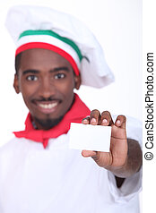 young black Italian cook showing a professional card