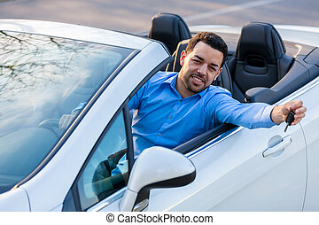 Young black latin american driver holding car keys driving his new car