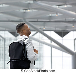 Young black man at airport with bag
