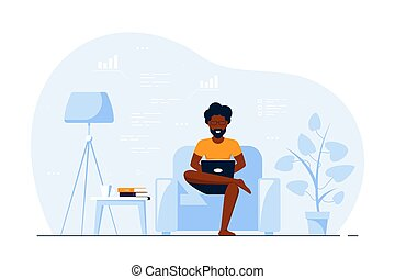 Young black man at home sitting in chair and working on computer.