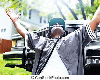 young black man in front of car with arms out
