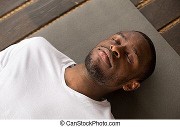 Young black man lying in Dead Body exercise