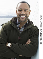 Young black man with smile on boat deck, leaning against wall with water in the background.