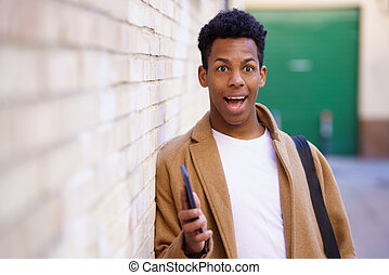 Young black man with a surprised look on his face in the street.