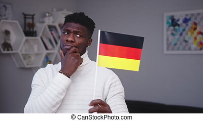 Young black man with german flag. Student exchange program or work relocation concept. High quality 4k footage