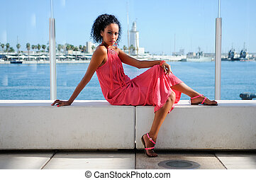 Portrait of a young black woman, afro hairstyle, wearing long pink dress, in the harbour