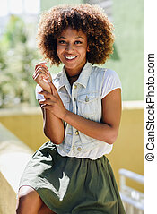 Young black woman, afro hairstyle, smiling in urban background