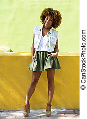 Young black woman, afro hairstyle, standing in urban background