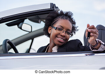 Young black woman driver holding car keys driving her new...