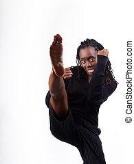 Young black woman fighting stance kick leg up