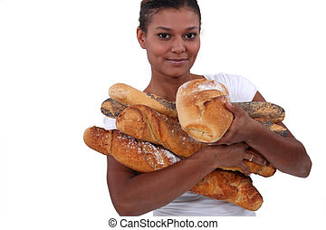 young black woman holding a lot of bread in her arms