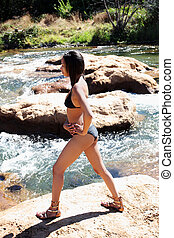 Young black woman in bikini on river bank