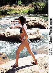 Young black woman in bikini on river bank
