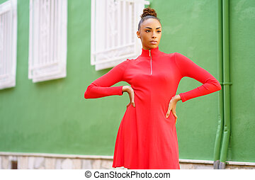 Young black woman in red dress in front of a green wall