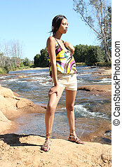 Young black woman in shorts by the river