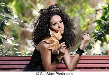 Young black woman in the park with a dry leaf
