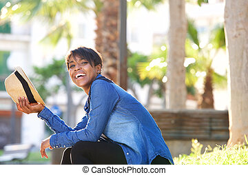 Young black woman laughing outside with hat