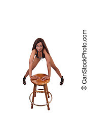 Young black woman leaning on stool in lingerie